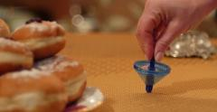 Blue Dreidel Spins near a plate of fresh baked holiday Hanukkah doughnuts Stock Footage