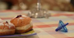 Camera pan from a static Dreidel to a plate of Hanukkah Doughnuts - stock footage