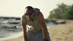 Tired male jogger taking break on beach, super slow motion 240fps  - stock footage