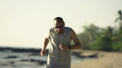 Tired man jogging on beach and taking break - stock footage