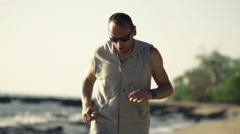Young jogger checking pulse on smartwatch on beach, super slow motion 240fps Stock Footage
