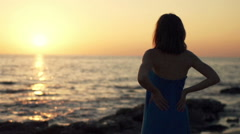 Young woman admire sunset while standing on beach, super slow motion 240fps - stock footage