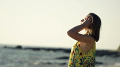 Young woman playing with hair on beach during sunset, super slow motion 240fps Stock Footage