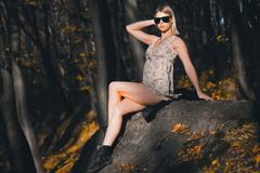 Stock Photo of Sexy girl lying on a rock in the forest, advertising clothes
