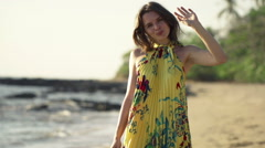 Happy, pretty woman waving hand and greetings to camera on beach Stock Footage