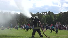 Fire fighter spray water from hose and kids run under water drops. 4K Stock Footage
