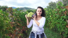 Vineyard at harvest time. Happy girl with basket walk amoung grapes rows, fro Stock Footage