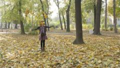 Older blond girl throwing yellow leaves,trying to attract attention younger kid Stock Footage