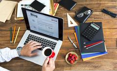 Blogger working at wooden desk Stock Photos