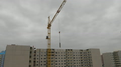 Cranes over unfinished buildings on construction site at a bright sunny day Stock Footage
