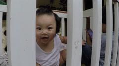 Baby girl creep and peep through crib railings - stock footage