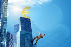 Businessman climbing skyscraper with euro sign - stock photo