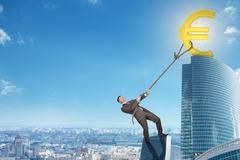 Man climbing skyscraper with euro sign - stock photo