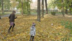 Sisters playing in the park by the autumn season,chasing ball through the leaves Stock Footage
