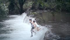 Girls jumping into waterfall Stock Footage