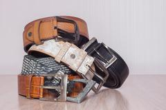 leather belt with a buckle on a wooden board - stock photo