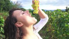 Beautirul girl tastes grapes outdoors at vineyard harvest, 4k crane shot Stock Footage