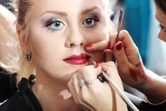 makeup artist applying lipstick on model lips with brush - stock photo