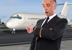 Handsome airline worker looking at his watch Stock Photos