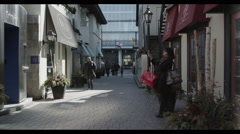 Dolly through Yorkville Toronto pedestrians in cool alley Stock Footage
