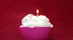 Cupcake with a candle on a bright red background Stock Footage