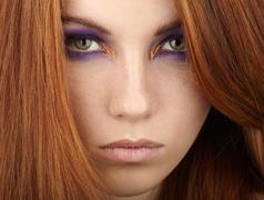 Young beautiful redhead woman with violet smokey eyes makeup Stock Photos
