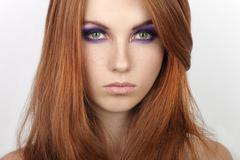 Young beautiful redhead woman with violet smokey eyes makeup Stock Photos