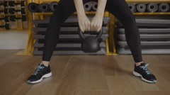 Young woman lifting kettle bell in gym Stock Footage