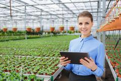 Pleasant greenhouse owner controlling her business - stock photo