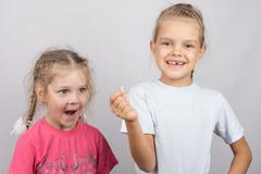Six year old girl showing her the other girl had fallen Milk front upper teet - stock photo