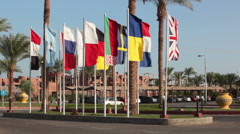International flags wave on the flagpoles near the hotel entrance, Egypt Stock Footage