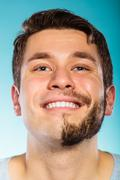 Stock Photo of Happy man with half shaved face beard hair.