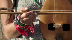 old european string instrument: young street artist woman playing a old string  - stock footage
