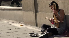 Beggar woman playing music and asking charity Stock Footage