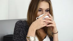 Stock Video Footage of Beautiful young girl drinking coffe in the kitchen. Close up