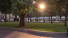 a public park in the afternoon with the sun throw the trees  - stock footage