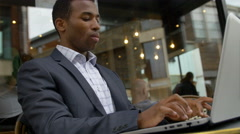 black businessman working with laptop in a cafe: cafeteria, outdoor  - stock footage