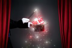 Magician hand with magic wand making Christmas  gift - stock photo