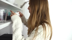 Sick young girl looking for medicine in the cupboard. Indoor photo - stock footage