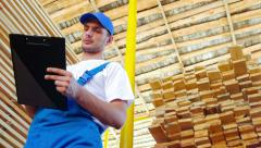 Young worker making an inventory of stock on wood Stock Footage