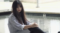 Sad asian woman during a rainy day: depressed young chinese woman Stock Footage