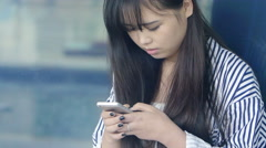 Young chinese girl texting messages on the cell phone Stock Footage
