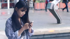 Young asian woman composing messages with a cell phone: texting messages  Stock Footage