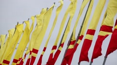 Red and yellow flags waving in a windy day. Stock Footage