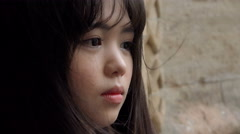 frightened and distressed young asian woman with the wind on the hair  - stock footage