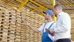 The seller helps the buyer to choose a good wood for building houses Stock Footage