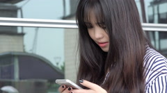 Young chinese woman making a phone call with her cell phone  Stock Footage