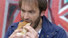 Hungry man eating a sandwich for lunch  Stock Footage