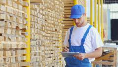 Employee of construction shop writes figures with a marker on wood Stock Footage