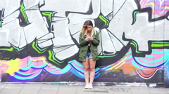 Young woman using smartphone leaning against a wall in the city: murals   Stock Footage